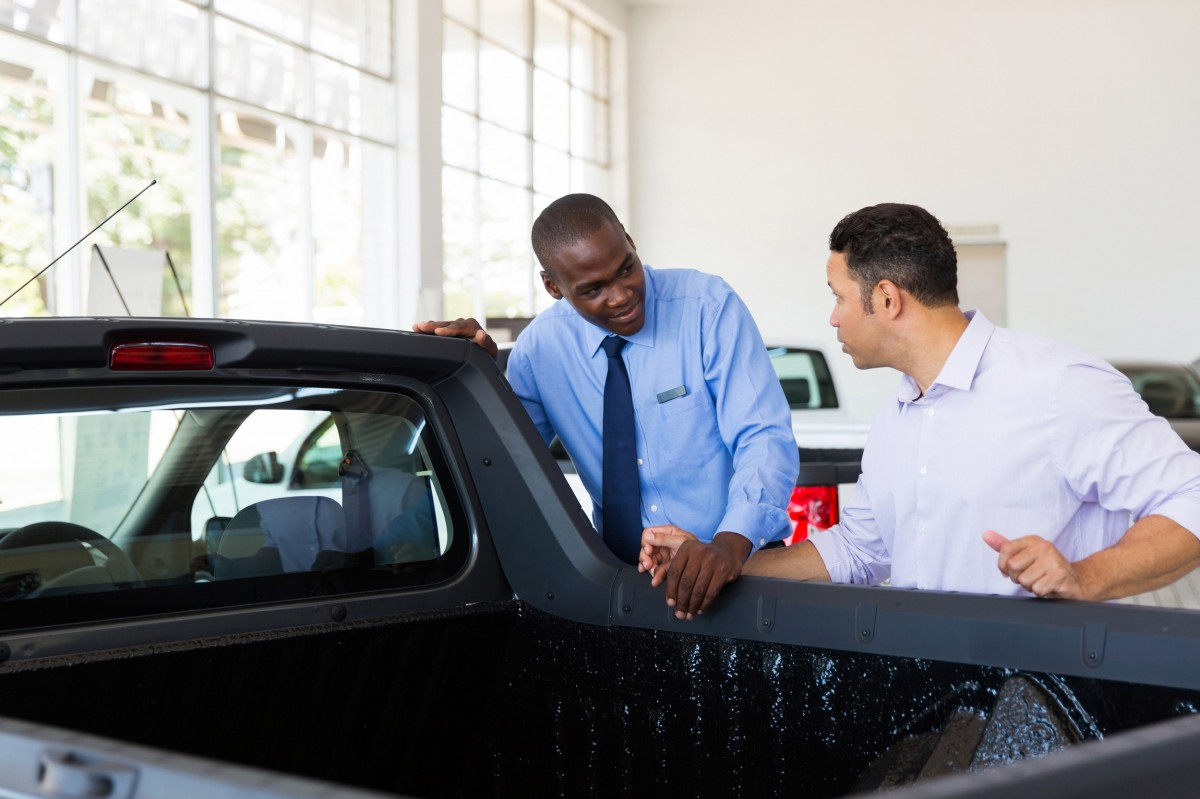 salesman talking to customer about a new vehicle